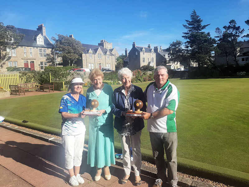 Mrs Graham and Mrs Smith presenting the trophies to Anne Robertson and Tam Terris