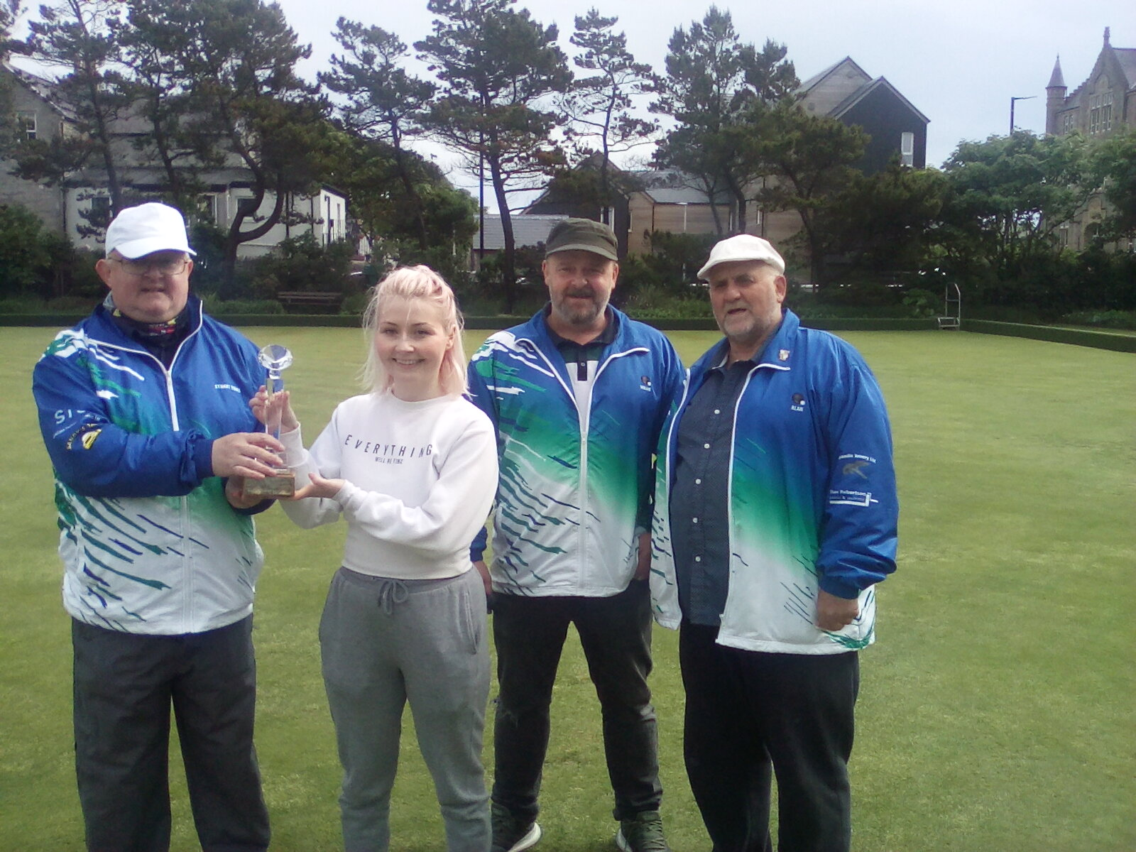 Stuart Terris of Shetland Technical Solutions presenting the trophy to Emma Moncrieff, Willie Coutts and Alan Smith