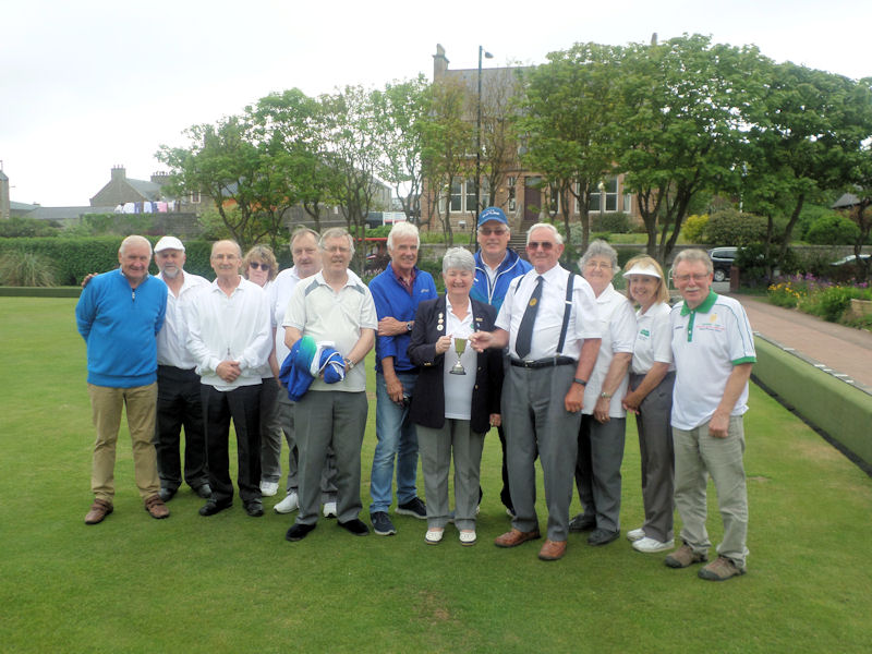 Gordon Stevenson accepting the trophy from the club President Elma Scott surrounded by the winning Morton Lodge team.