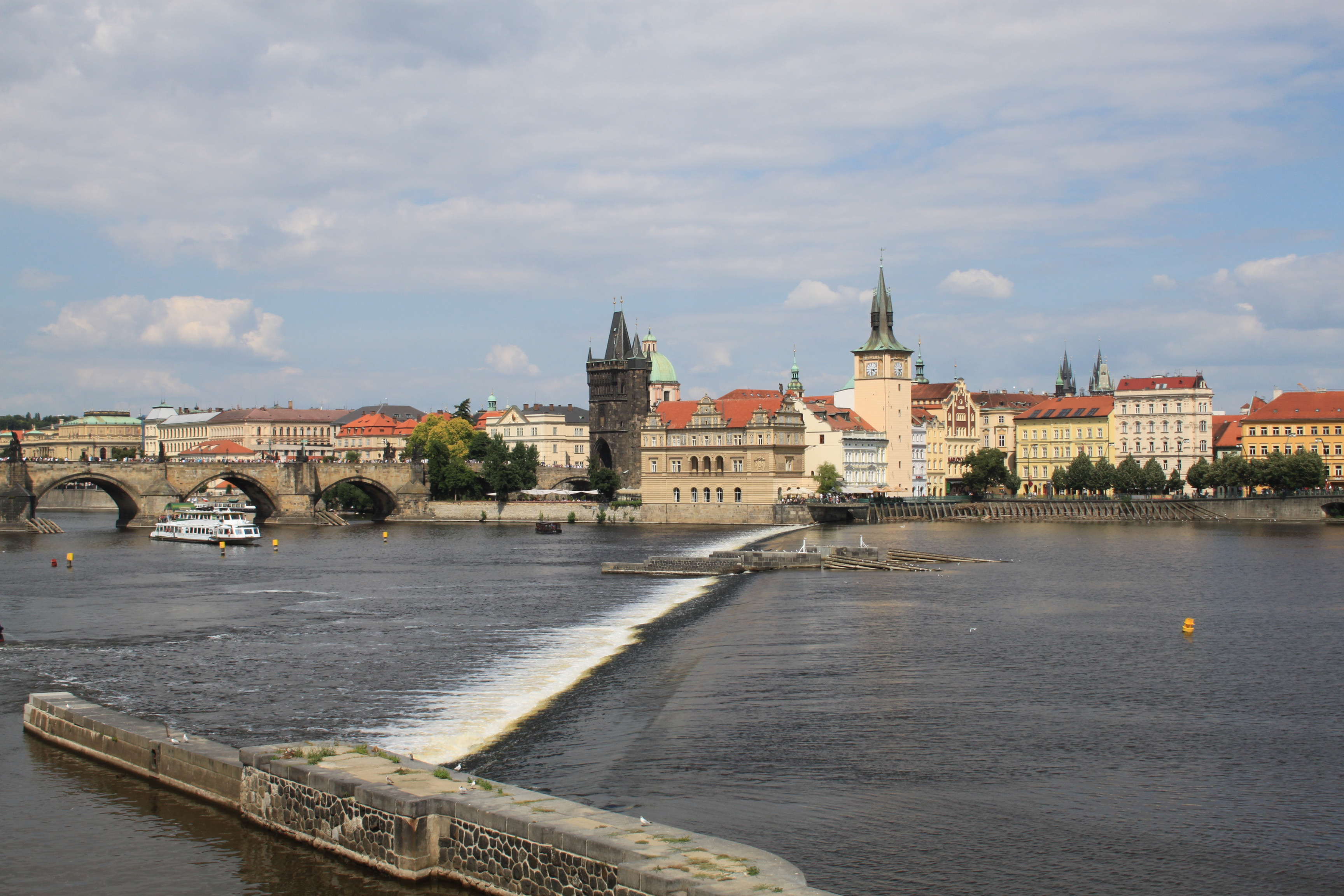 View of Prague across river with weir, Charles Bridge and landmark buildings