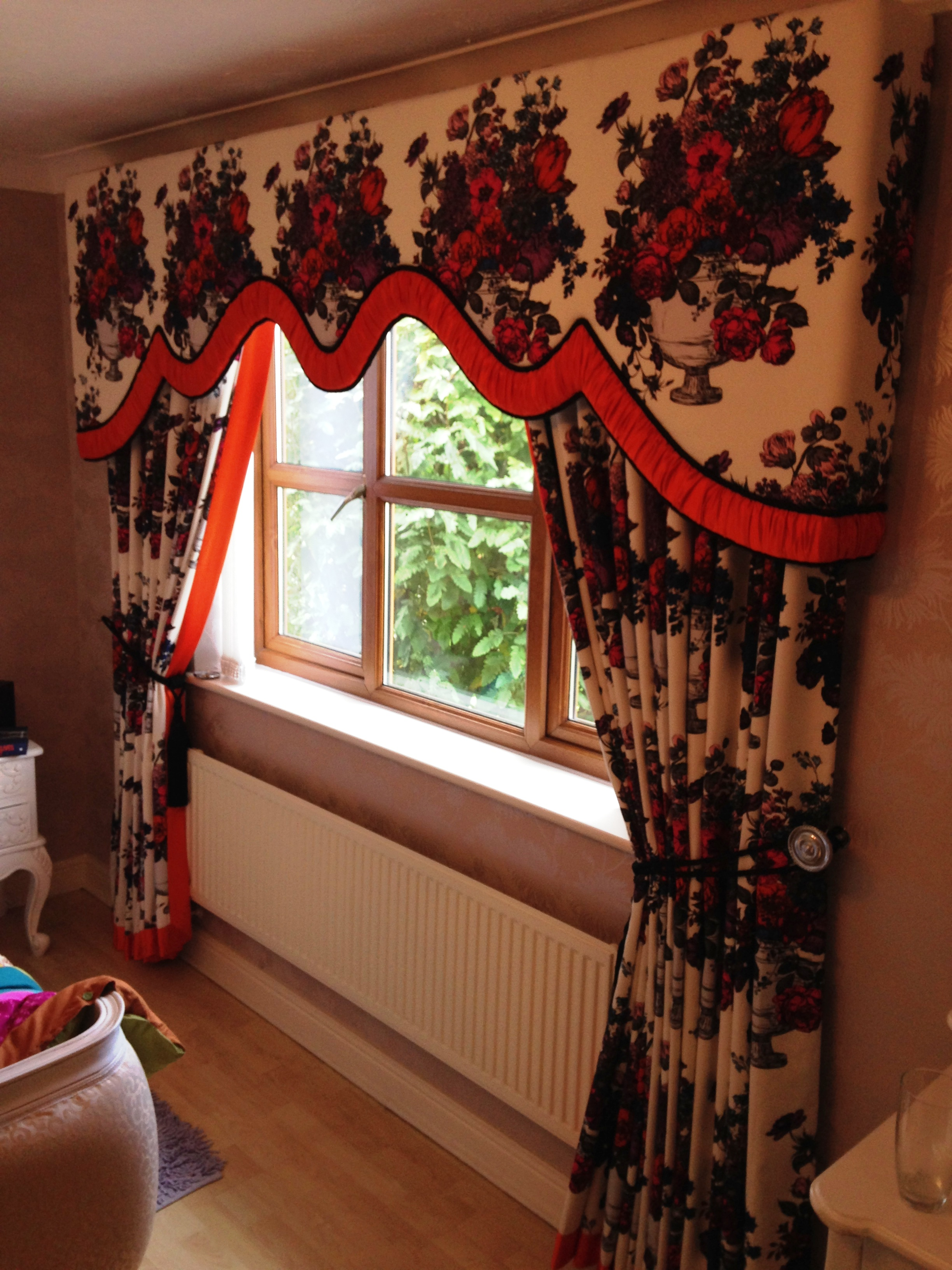 pelmet in flowery fabric with bright orange ruched border and matching curtains