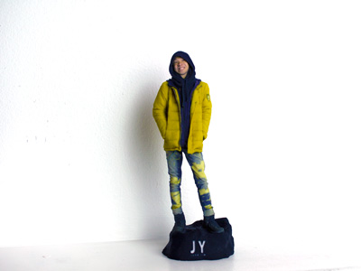 Boy in yellow jacket and black hood on the black rock base